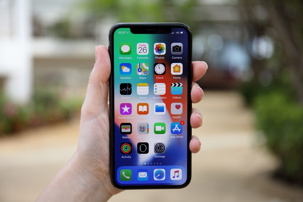 Woman hand holding iPhone X with IOS 11 on screen